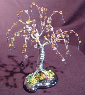 Made of 26 gauge galvanized steel wire with yellow, white and green colored fringe beads that are wired onto each branch. Mounted on a piece of free formed solid glass using sea sand and a bonding age