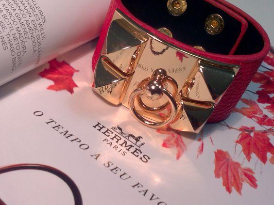Bracelete vermelho estilo Hermés com detalhes de metal dourado e fecho de pressão.