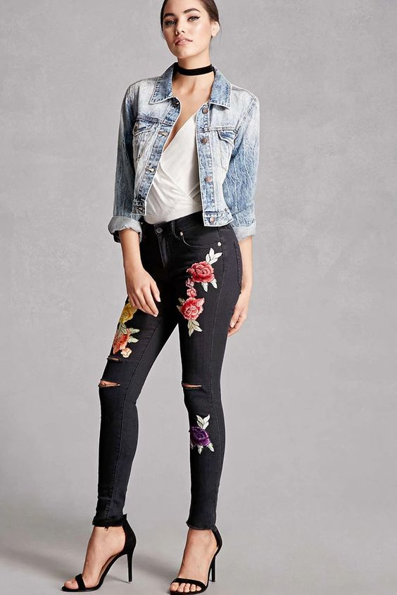 A pair of mid-rise skinny jeans featuring front embroidered floral patches, ripped knees, a frayed hem, five-pocket construction, and a buttoned zip fly. This is an independent brand and not a Forever 21 branded item.