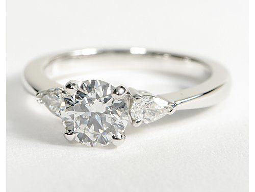 Round solitaire engagement ring with pear-shaped diamonds - I love pear shaped diamonds.  Don't they look lovely next to the round center stone?