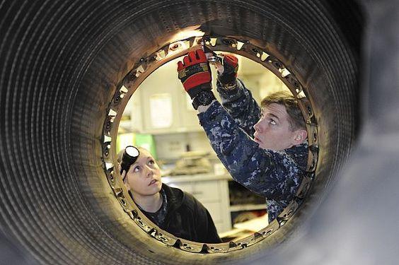 Aviation Machinist's Mate Airman Michael Walsh and Aviation Machinist's Mate Airman Chandra Tremayne perform maintenance on a 404-400 jet engine afterburner aboard the aircraft carrier USS Nimitz (CVN 68).