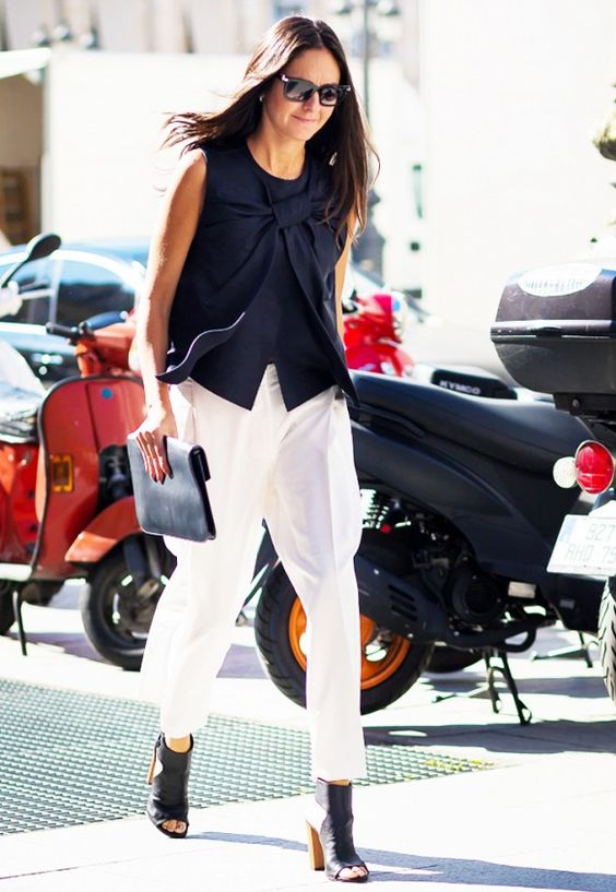 A black sleeveless tank is worn with white trousers, black peep-toe heels and a black clutch.