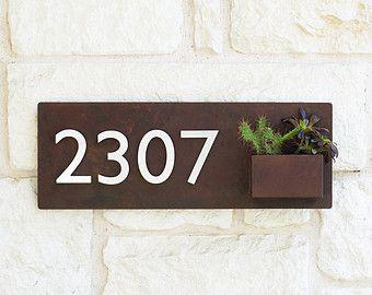 Bienvenido a casa. Este plantador de la pared dirección moderna placa y canal añade elegancia y estilo a la fachada de su casa con los números de