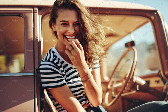 Portrait of beautiful young woman laughing in the car. Woman taking a break on road trip. #lifestyle #photography #woman #adventure #travel #vintage #happy