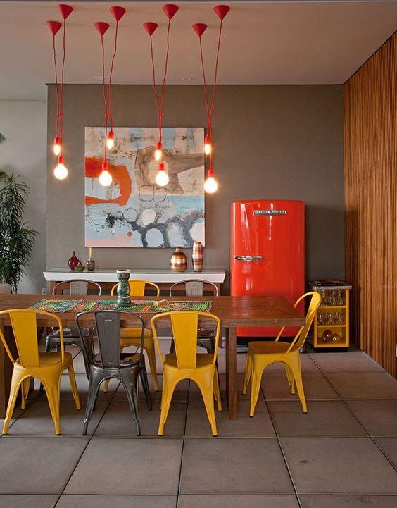 A decoração dessa cozinha e jantar integrados, no famoso edifício 360 º, no Alto da Lapa, tem geladeira laranja e cadeiras amarelas. A decoração do apartamento, com pendentes e estruturas a mostra, é toda com perfume do estilo industrial! Clique para ver mais: