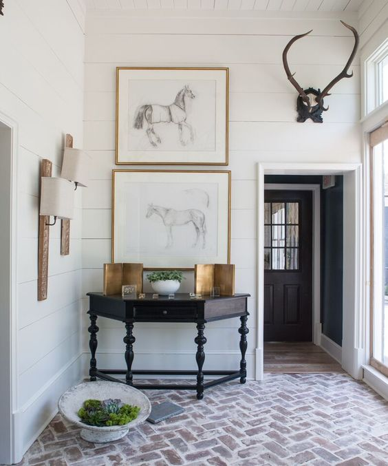 Antique Demi-lune table, framed charcoal horse sketches, reclaimed wood sconces with linen shades, black-forest mounted horns, brick zig-zag floor ... all fabulous!:
