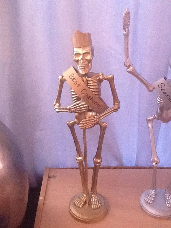 Dollar Store Skeletons as costume awards... a little spray paint and hot glue: Great idea!