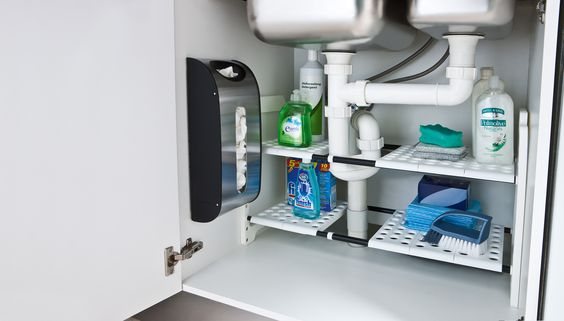 Organise your kitchen.Under the sink organisers. Featuring the expandable under sink shelf ($49.95) and the simplehuman grocery bag holder. Both products available at Howards Storage World.