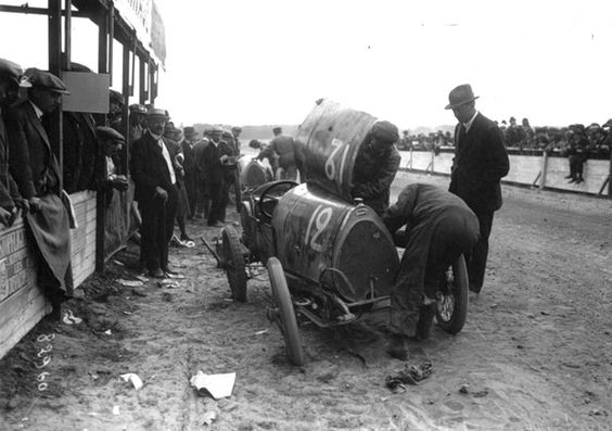 """Michele Baccoli's Bugatti T13 takes a pit stop during the """"VIII Coupe des Voiturettes"""" held on 29 August, 1920 at the Circuit de la Sarthe Circuit (Le Mans). Baccoli finished fifth. Note that only the driver and the riding mechanic were allowed to work on the car, and the trusting official watching on is standing ion the racetrack. Roads were largely unpaved, as were racetracks."""