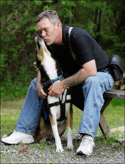 Service dogs help local soldiers battling PTSD. U.S. Army Spc. Mike Ballard poses for a photo with Apollo, his service dog, Friday, May 17, 2012, in Puyallup, Wash. (AP Photo/Ted S. Warren)