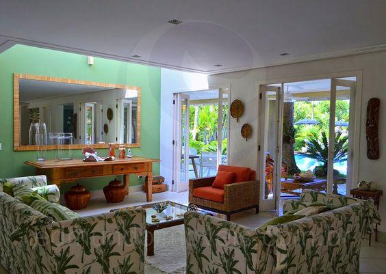 O aparador em mármore e madeira divide este ambiente com o living room, decorado por um belo par de sofás estampados com motivos florais em tons de verde.