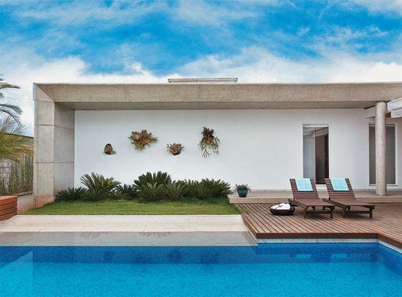 O deck de cumaru faz a ligação dela com o corredor externo que leva aos quartos e com a área de lazer. Pastilhas de porcelana revestem a piscina.