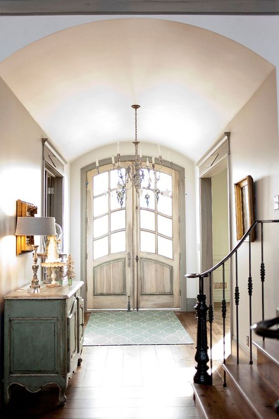 French Country style in a country home inspired by Europe. Heavenly sunshine floods the front entry hall of a French Nordic, French Country style hallway with barreled ceiling and blue grey stained trim.#frenchcountry #interiordesign #decorideas #entry #frontdoor #archeddoors #barrelceiling #staircase