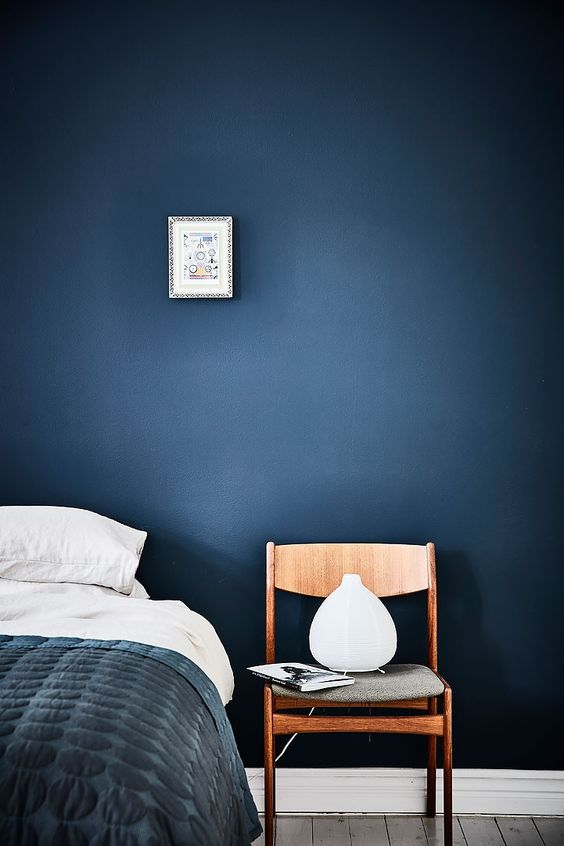 dark blue wall in the bedroom. Looks great with white and wood. Love the wooden…