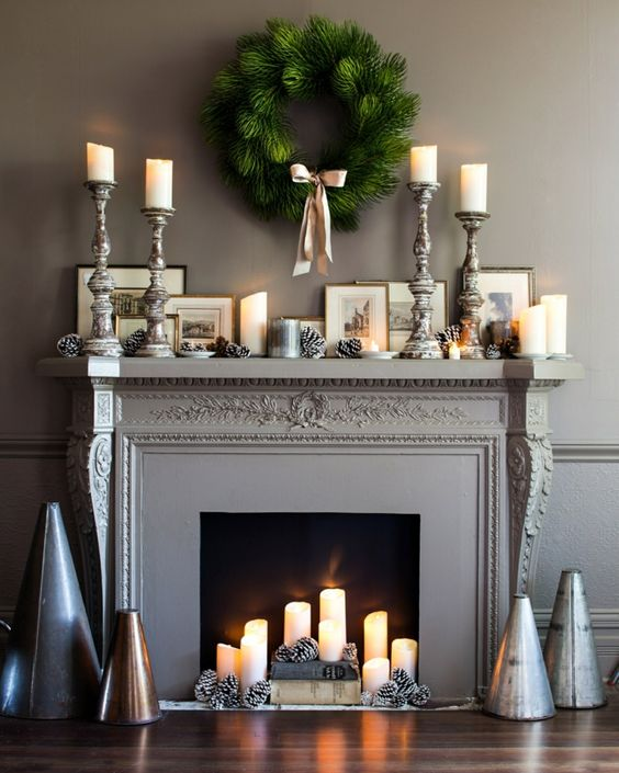 fausse cheminée décorative, manteau de cheminée gris, plusieurs bougeoirs, cônes peints en argent