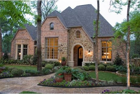 Brick and stone frame an arched doorway. Lush landscaping complements a custom walkway. Highland Homes, The Sienna Plantation community near Houston.