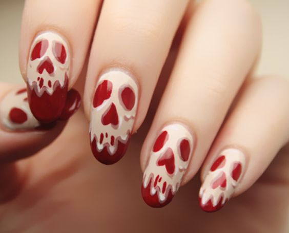 Skeleton faces on bloody red nails Halloween nail art design. Spice up your costume by drawing spooky skeleton faces on top of your bloody red nail polish base coat.