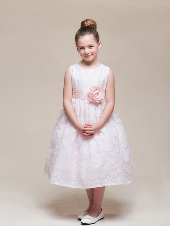 sleeveless dress with lace overlay and round flower at the waist.. Available in Ivory and Pink.