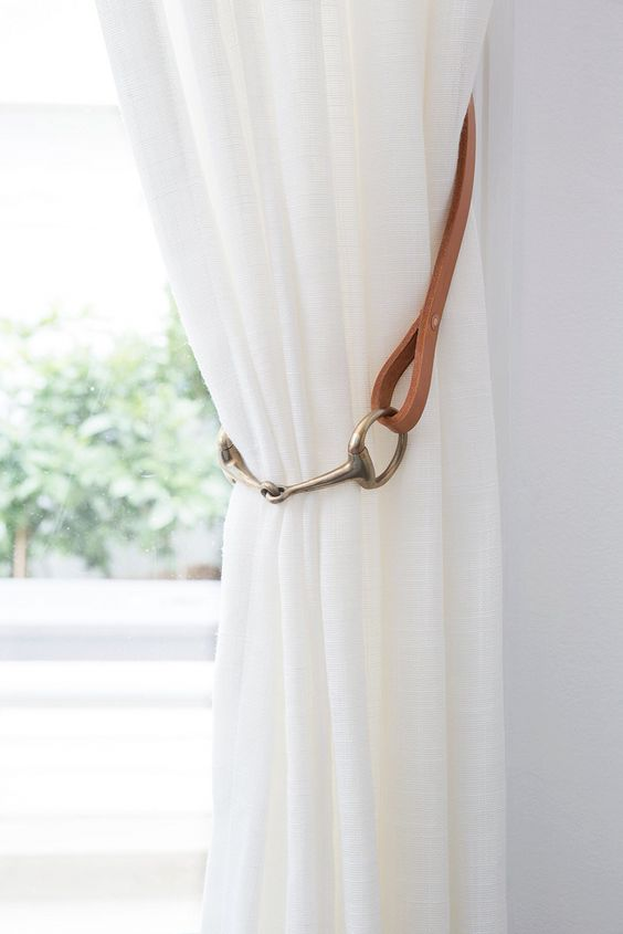 Curtain Tiebacks by Shakespeare Design. The stunning natural beauty of tan leather coupled with a brass horse bit adds texture and a stunning feature to sheer white linen curtains. Enquiries to www.shakespeare-design.com.au: