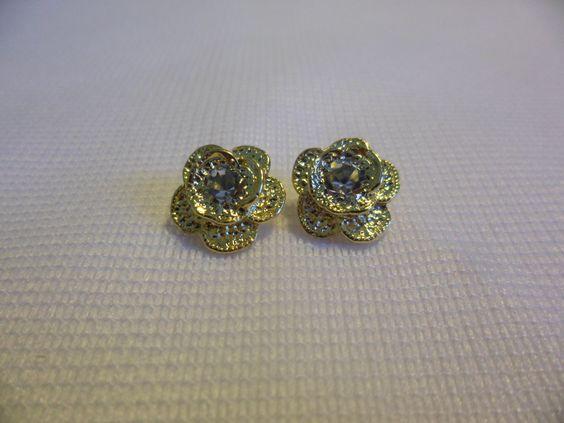 Brinco flor c/ cristal Acabamento: folheado em ouro 18k  Dados técnicos: 14 mm de diâmetro.  Duas pedras de strass Garantia de 1 ano.  Preço: R$ 20,00