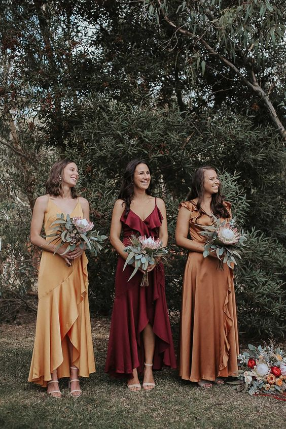 Rust Wedding Color Ideas For Cozy Fall Weddings, mix matched long bridesmaid dresses in autumn tones #longbridesmaiddresses #autumnbride #autumnwedding #autumntones #mismatchedbridesmaids