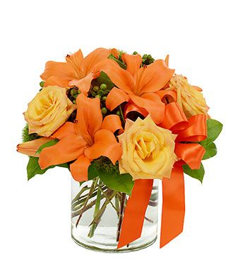 Orange asiatic lilies, yellow roses and green hypericum in circular vase: