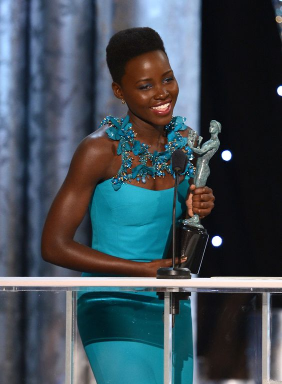 Nominee Lupita Nyong'o wore a Gucci One of a Kind turquoise silk crepe column gown with gold and turquoise floral embroidered straps for the 20th Annual Screen Actors Guild Awards taking place at the Los Angeles Shrine Exposition Center.