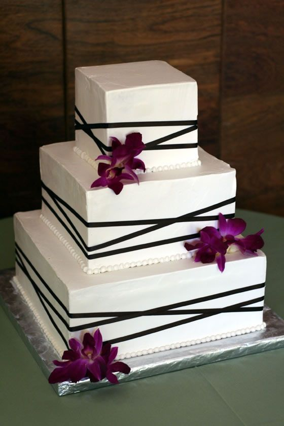 A square wedding cake wrapped in brown ribbon with fresh purple dendrobium orchids. By True Confections.