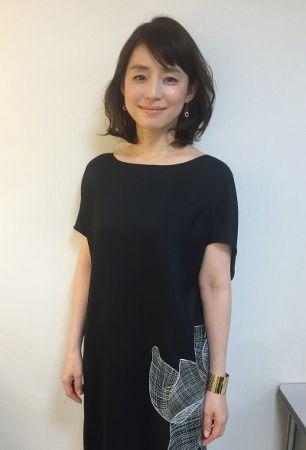 白いイラストが描かれた黒いワンピースを着た石田ゆり子