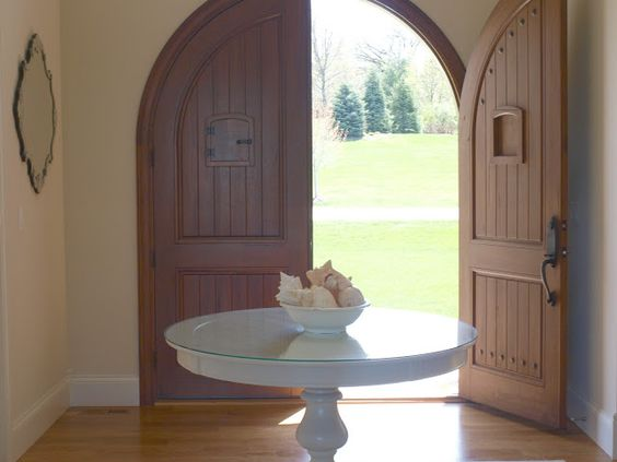 Custom Andean walnut arched double doors with speakeasies/Serene and timeless entry in European country house with Nordic French style/foyer/round table with bowl of conch shells/Venetian mirrors/white oak flooring/Hello Lovely Studio
