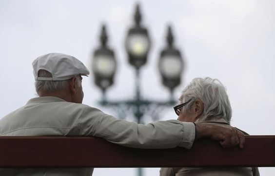 A retired couple sits on a bench in Enghien-les-Bains - REUTERS/Christian Hartmann