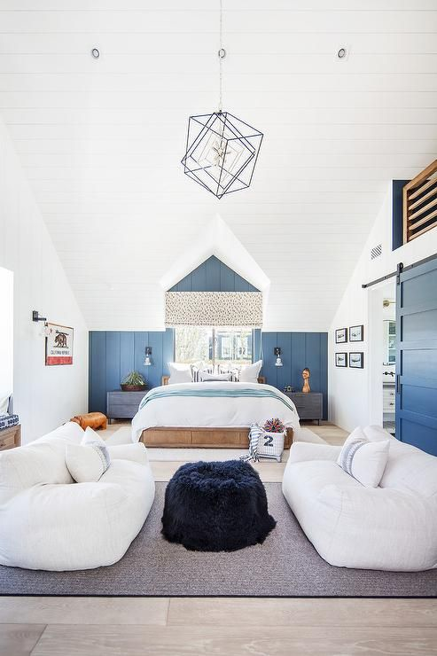 White bean bag sofas sit beneath a vaulted shiplap ceiling on a gray rug facing a black faux in a kid's bedroom lounge area.