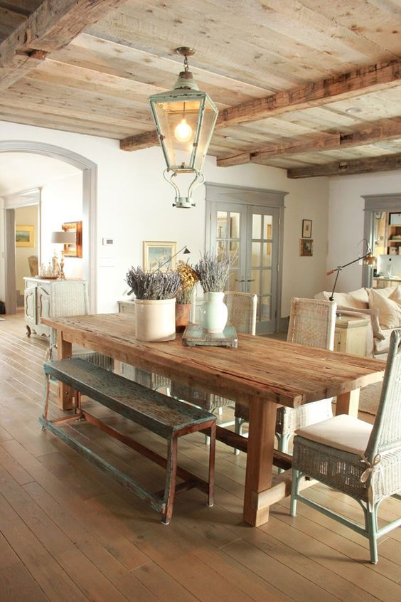 Rustic decor in a charming dining room with French farmhouse decor. Rustic farm table topped with stoneware holding lavender, knotty wood ceiling, vintage lantern, and blue grey trim throughout this home by Desiree Ashworth of Decor de Provence. #frenchfarmhouse #vintagelantern #rusticdecor #diningroom #frenchcountry