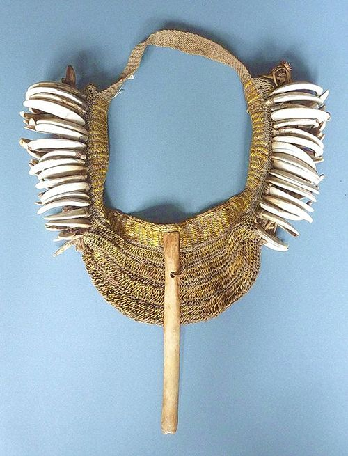 This is a rare bag from the western part of the island of New Guinea, now under control of Indonesia, and generally referred to as Papua. The piece is made of boars' tusks and fibre, including orchid fibre (yellow). The cassowary bone which is prominent at the front and sticks out at the bottom must have a special meaning which even despite research carried out seems to be unknown today. (Joost Daalder)