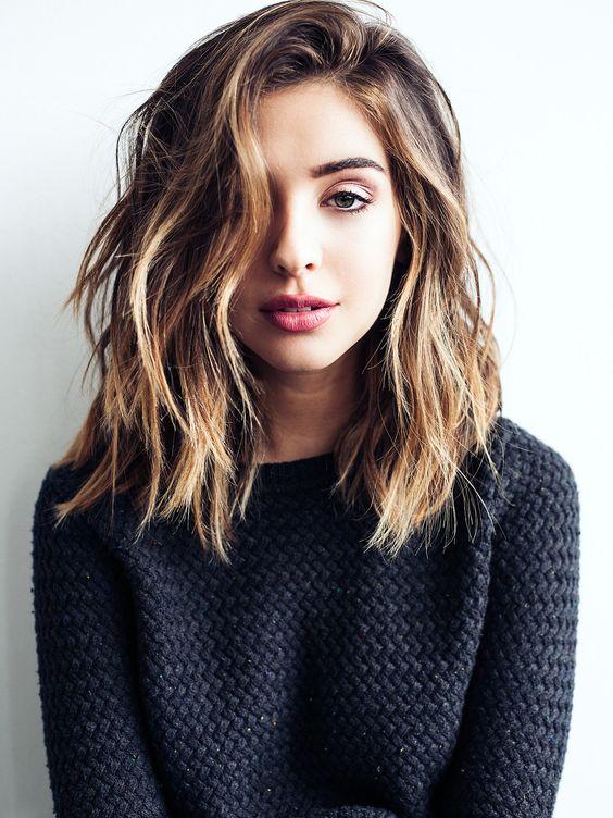 Chica usando un corte de cabello long bob en capas lacio pero despeinado con un tono de tinte de mechas