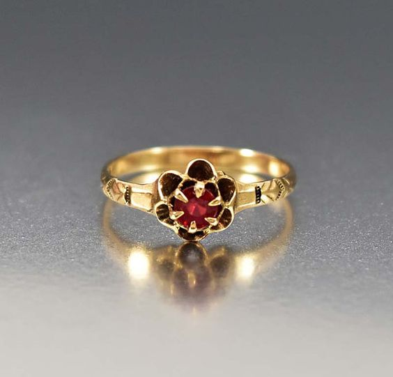 Eine schöne feminine antike viktorianische Ring, um 1900, mit einer Butterblume Blume Fassade zentriert mit einem roten Rubin. Gerendert in einem feinen 12K rose Gold, ist der Rubin offen so dass wieder eine schöne regal Farbe zu blinken beim tragen. Eine schalenförmige und geriffelte scharfe Hahnenfuß bildet den perfekten Rahmen um den Rubin zu präsentieren.  Rubine wecken die Sinne, rühren Sie die Phantasie und Gesundheit, Weisheit, Wohlstand und Erfolg in der Liebe garantieren sollen…