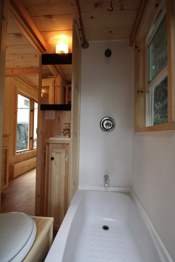 Tiny home packs storage stairs, 2 lofts, tub in 136 sq ft: