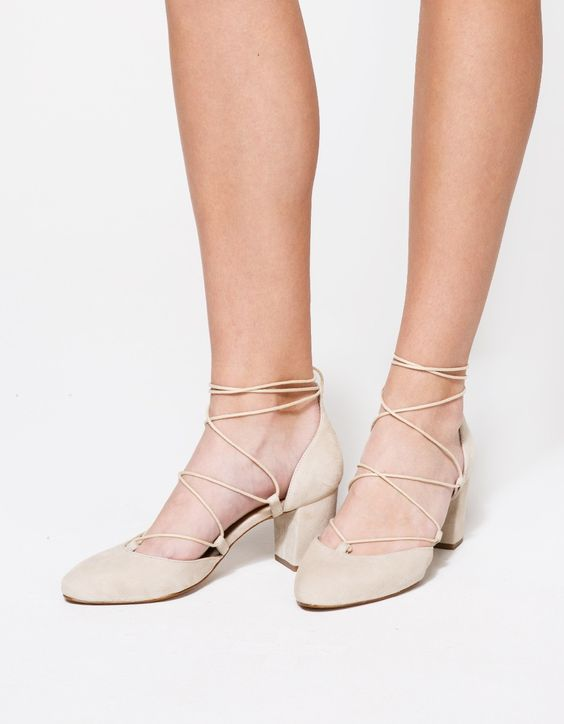 From Intentionally Blank, a classic suede wrap around heel in Nude. Features round toe, matching wraparound lace up, leather uppers, leather lining, leather heel and synthetic outsole.  •Suede wrap around heel in Nude •Roundtoe •Matching wraparound