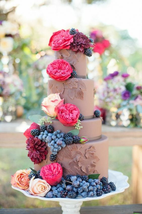 Chocolate wedding cake with fresh berries and flowers.: