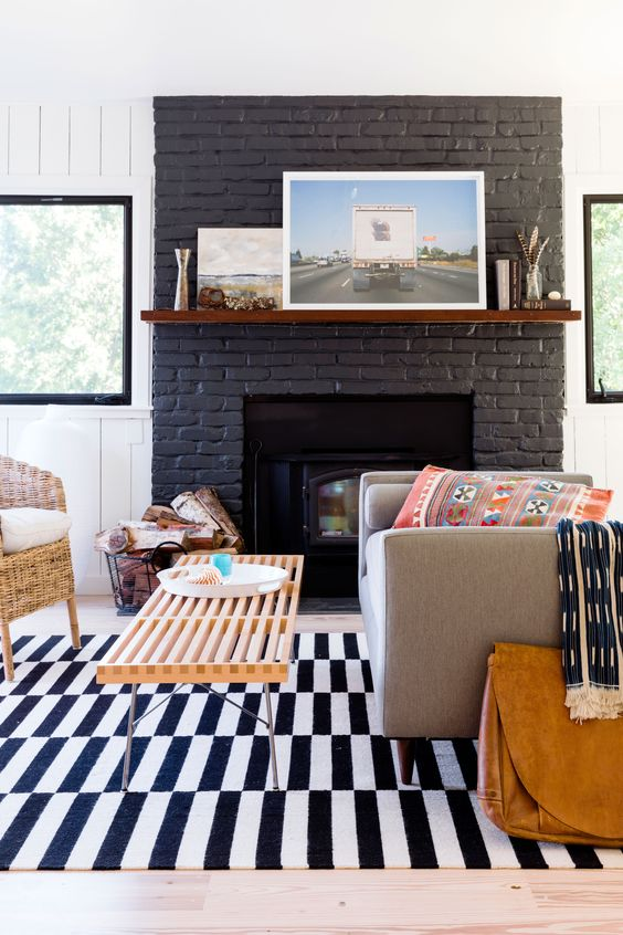 Play up Contrasts In the living room, dark accents amplify the lightness of the house and its surroundings. Black-framed windows, free of curtains, turn the view into artwork. The couple painted the living room's brick fireplace charcoal for a more modern look.