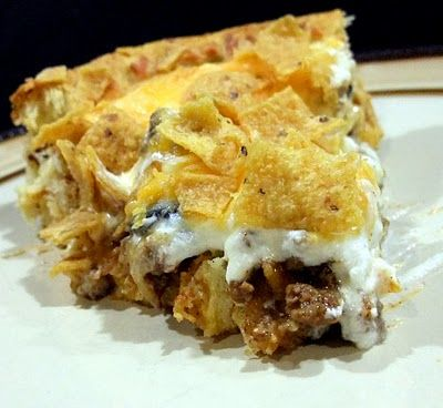 SENSATIONAL TACO PIE  1- 1 1/2 lb. ground beef  1 pkg. taco seasoning mix  1/2 c. water  1 (4 oz.) can sliced olives  1 can crescent roll dough  1 c. sour cream  1 c. shredded cheddar cheese  2 c. crushed corn chips