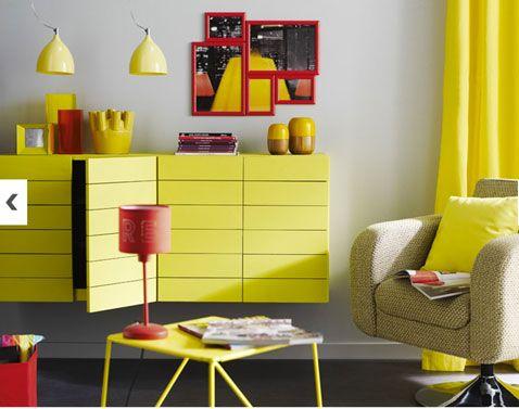 Deux couleurs tendances pour ce salon : gris galet pour les murs, jaune citrine pour le buffet, la table et les rideaux. Quelques touches de rouge viennent couper un peu cet univers bicolore.