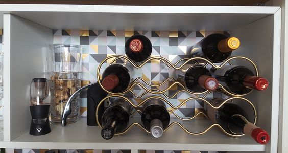 Wine rack in IKEA Valje cabinet bar painted with shiny gold spray paint to match decorative paper. Two wine racks from Howard's storage world in Dublin. 20 EUR each