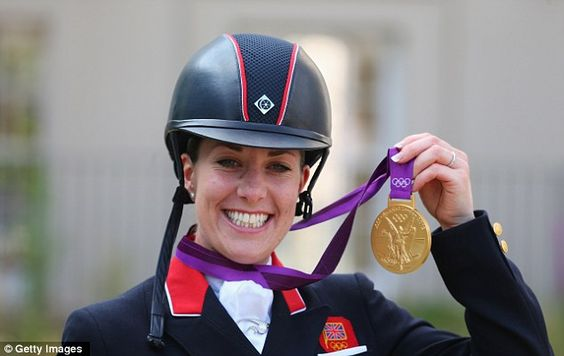 Triumphant: Charlotte Dujardin shows off her gold medal after the individual dressage