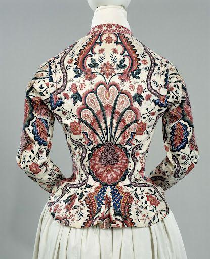 Jak van sits, dat op een crèmekleurig fond grote bloemen en ruitpatronen toont, met als hoofdkleuren paars, roze, blauw en blauwgroen. Afwerking met roze-wit langettenband., anoniem, 1810 - 1820. Hindeloopen