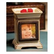 Snapshot – A beautiful way to make your family photos shine as fondly as the memories they encapsulate. Once the Scentsy warmer, Snapshot, is switched on, a picture window placed in a square, ivory and taupe column radiates light from within its ropy, silver frame. $35.00