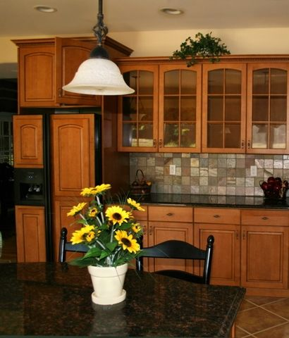 The slightly darker than honey we can see here is complimented well with dark colors everywhere from the furniture to the appliances. It definitely helps to tie in the black granite that covers everything else.