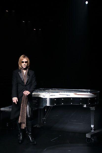 黒いグランドピアノの横に立っているXJAPAN・YOSHIKIの画像