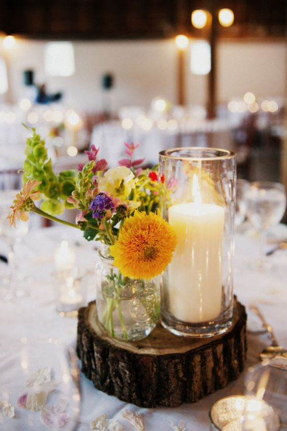 Love these centerpieces.  Mason jars and simple white candles on a rustic wood platform.
