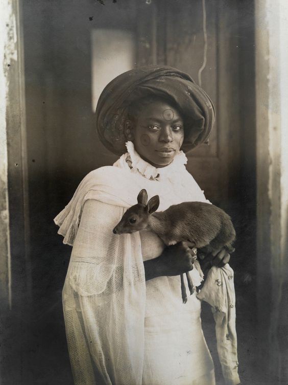 A young Kenyan woman holds her pet deer in Mombasa, Africa; March, 1909. Photograph by Underwood and Underwood